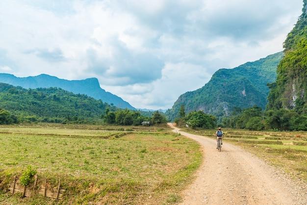 風光明媚な風景の未舗装の道路上の女性乗馬マウンテンバイク