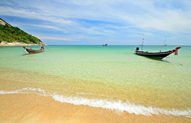 透明な水、タイの熱帯のビーチターコイズブルーの海に浮かぶボート