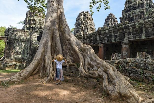Один турист, посещающий руины ангкора среди джунглей