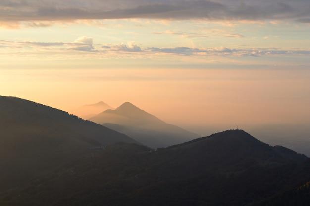 秋のアルプス、岩が多い山頂と尾根の頂上からの夕日