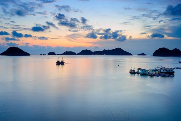 ベトナムのキャットバ湾の海、雲模様の熱帯気候、カラフルな空、水平線に浮かぶ島々に浮かぶ漁船と夕暮れ時。長時間露光