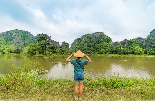 田んぼの中で岩の尖塔を持つ草原にベトナムの帽子を持つ女性