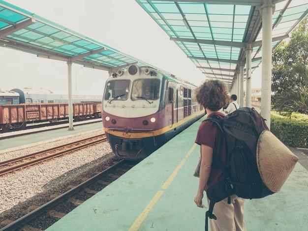 ベトナムの駅でプラットフォーム上の女性バックパッカー待っている電車。休暇中に電車で旅行する一人。世界中をさまよう冒険。