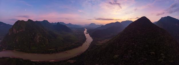 ドローンからの空中のユニークな眺め:ムアンゴイラオスのナムオウ川渓谷、夕焼けのカラフルな空、ドラマチックな山の風景、東南アジアの旅行先