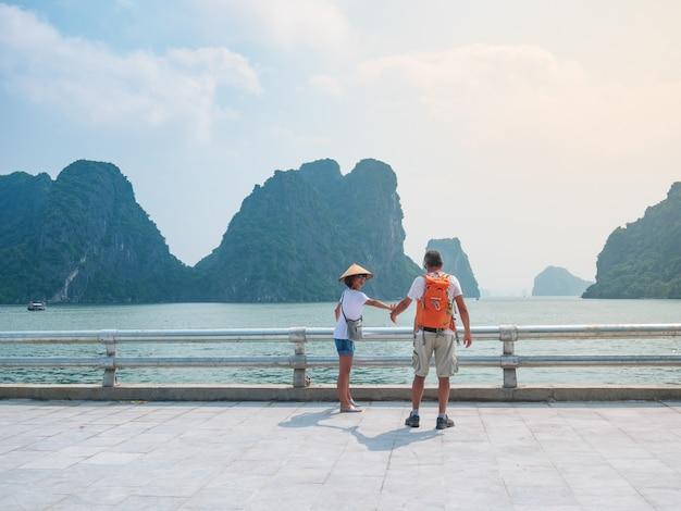 ベトナム、ハロン市の遊歩道で手をつないで歩くカップル、海のハロン湾の岩の尖塔の眺め。男と女が休暇で一緒に有名なランドマークに旅行を楽しんでいます。