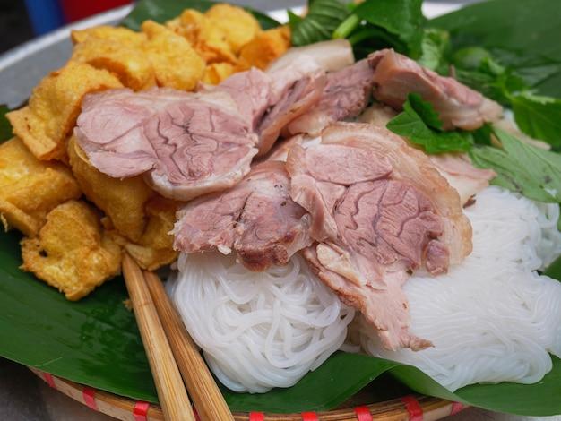 Бун ча, традиционное вьетнамское блюдо, подается на обед в качестве уличной еды в ханое. фарш из свинины, жареный рис, тофу, лапша, травы на банановом листе и суп.