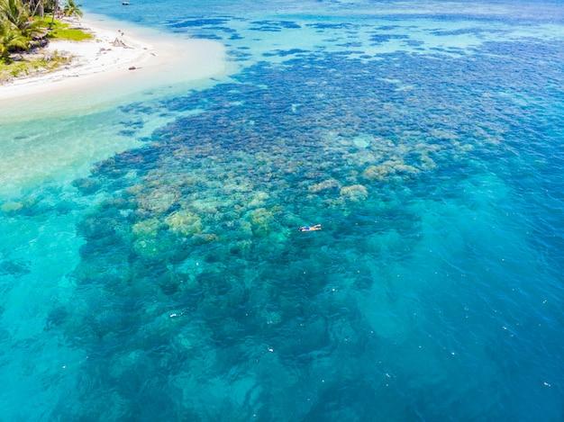 サンゴ礁の熱帯のカリブ海、ターコイズブルーの水でシュノーケリングの人々を下の空中。インドネシアバニャック諸島スマトラ、観光ダイビング旅行先。
