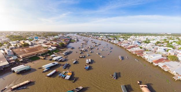 日の出のカイラン水上マーケット、南ベトナムのメコンデルタ地域、観光地カントー川で卸売果物や商品を販売するボートの空撮。