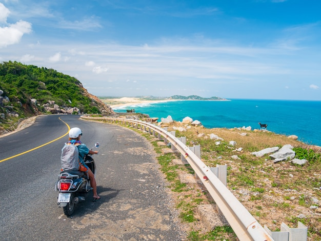 ニャチャンクイニョン、フーイエン省の豪華な海岸の景色を見て曲がりくねった道でバイクに乗っている一人、ベトナム旅行