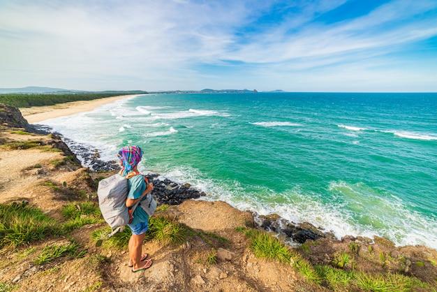 上記の崖から熱帯海岸を見てバックパックを持つ女性。ベトナム旅行先、ダナンとニャチャンの間のフーイェン県。豪華な黄金の砂浜の青い海