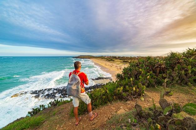 上記の崖から熱帯海岸を見てバックパックを持つ男。ベトナム旅行先、ダナンとニャチャンの間のフーイェン県。バイセップゴージャスビーチ