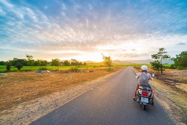 プーイェン県のビューマウンテンを見るバイクの一人、ニャチャン・クイニョン、ベトナムを旅する冒険。日没時のリアビューサンバースト劇的な空。