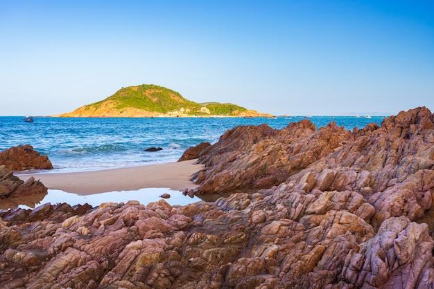 Великолепный тропический пляж, бирюзовая прозрачная вода, уникальные каменные валуны, камрань нячанг, вьетнам, юго-восточное побережье, туристическое направление, пустынный пляж, без людей, ясное голубое небо.