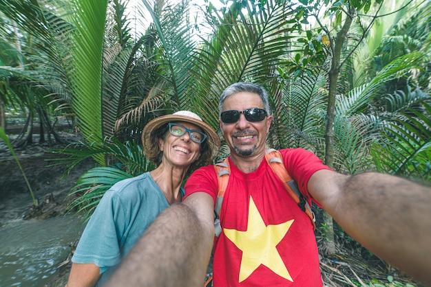 Пара принимая селф. мужчина и женщина в регионе дельты меконга, южный вьетнам. пышные зеленые кокосовые пальмы, лесистая местность и водные каналы