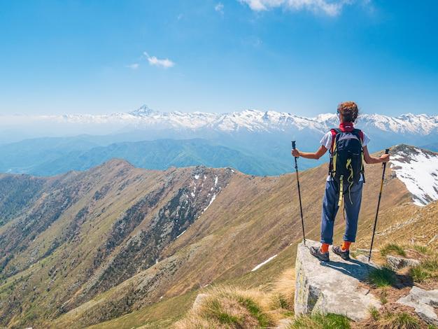 Женщина с рюкзаком на вершине горы