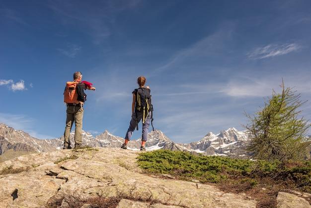 Пара с рюкзаком на вершине горы