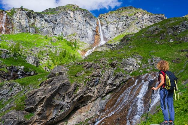 山の滝を見てハイカー
