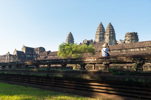 Один турист, посещающий руины ангкора среди джунглей, храмовый комплекс ангкор-ват, туристическое направление камбоджа. женщина в традиционной шляпе, вид сзади.