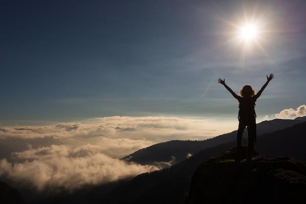 山の頂上で腕を太陽に持ち上げた女性、渓谷の劇的な風景の雲。