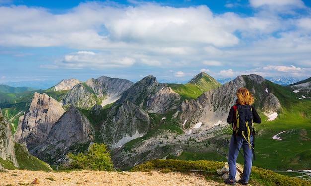 ビューを見て山の頂上で休んでバックパックを持つ女性