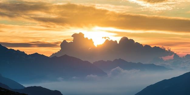 日の出のアルプス。カラフルな空の雄大な山頂、霧の霧の谷。