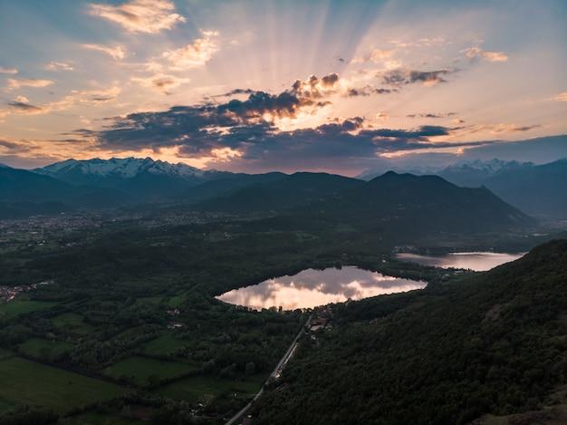 日没時の湖、雪を頂いた山脈の反射、風光明媚なカラフルな空、雲の向こうの太陽光線。