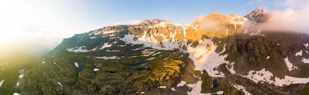 Высокогорный альпийский пейзаж с величественными скалистыми горными вершинами. воздушная панорама на рассвете. альпы, анды, гималаи