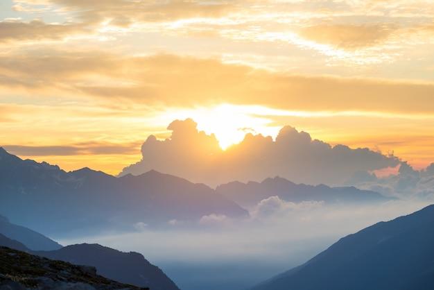 日の出のアルプス。カラフルな空の雄大な山頂、霧の霧の谷。上からのサンバーストとバックライトの広大な眺め。