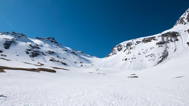 春のアルプス、晴れた日の雪景色のスキーリゾート、高山のアーチの高い山頂、雪崩の危険。