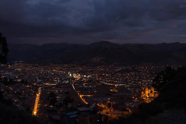 夕暮れ時に輝く街の明かりとクスコの町のパノラマビュー