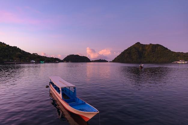 バンダ諸島の熱帯の海の木製ボートを日没インドネシアのモルッカ諸島。人気の旅行先、最高のダイビングシュノーケリング、火山。