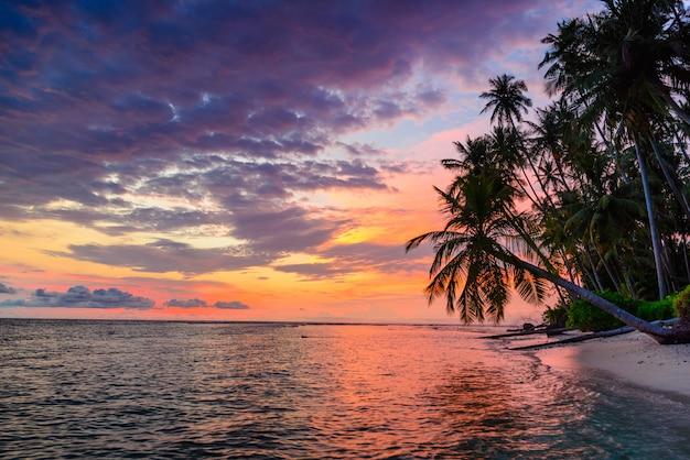 熱帯の砂漠のビーチ、海に劇的な空の夕焼け