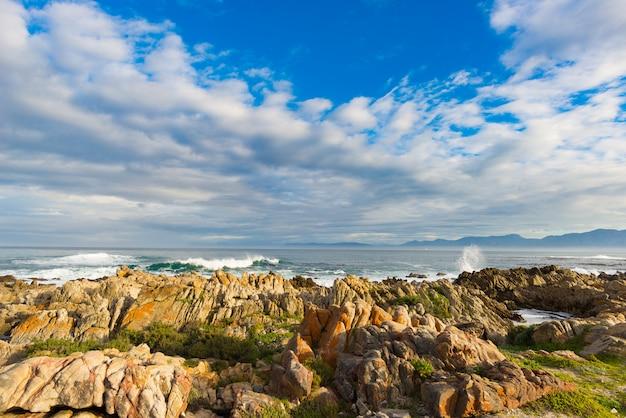ホエールウォッチングで有名な南アフリカのデケルダースの海の岩の多い海岸線。冬の季節、曇りの劇的な空。