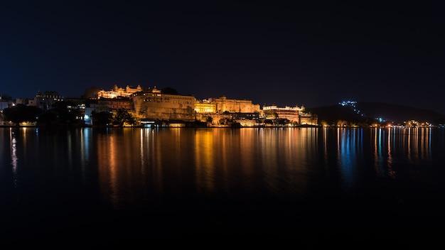 夜のウダイプールの街並み。インド、ラジャスタン州の旅行先であるピチョラー湖の光を反射する壮大な都市宮殿。