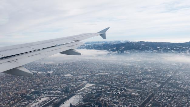 トリノの空撮。イタリア、トリノの街並み。冬、霧と雲のスカイライン。スモッグと大気汚染。