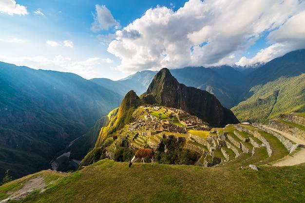 Мачу-пикчу освещается теплым закатным светом. широкий угол обзора с террас выше с живописным небом и солнцем взрыв.