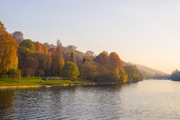 ポー川とカラフルな木を見下ろす丘の上の教会と秋の夕暮れ時のトリノ(トリノ-イタリア)の街の景色。