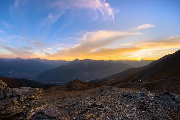 日没時のイタリアのフランスアルプス。雄大な山頂、乾燥した不毛の地形、緑の谷の上のカラフルな空。