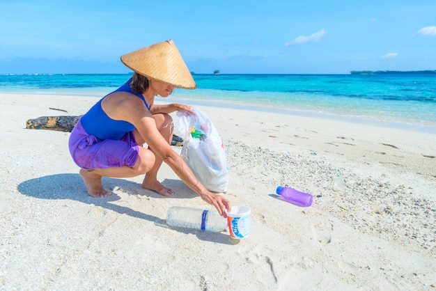 美しい熱帯のビーチ、ターコイズブルーの海でペットボトルを集める女性