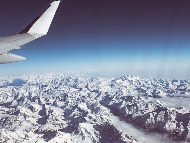 一般的な飛行機の翼を持つ冬のイタリアのスイスアルプスの空撮。雪を頂いた山脈と氷河。広大な眺め、澄んだ青い空。
