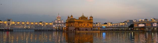 インドのパンジャブ州アムリトサルにある黄金寺院は、シーク教の宗教の中で最も神聖な象徴であり、崇拝の場所です。夜に照らされ、湖に反映されます。