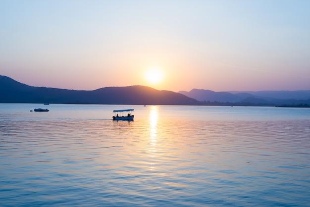 ピチョラー湖に浮かぶボートは、丘の向こうの水に反射してカラフルな夕日を見せます。インド、ラジャスタン州ウダイプール。
