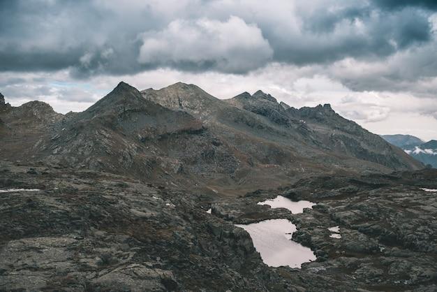 高地の岩の多い風景と小さな湖。劇的な嵐の空と雄大な高山の風景。上から広角ビュー、トーンイメージ、ビンテージフィルター、スプリットトーン。