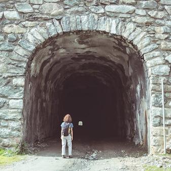 トンネルの入り口で歩いている女性。トーンの画像、ビンテージフィルター、スプリットトーン。