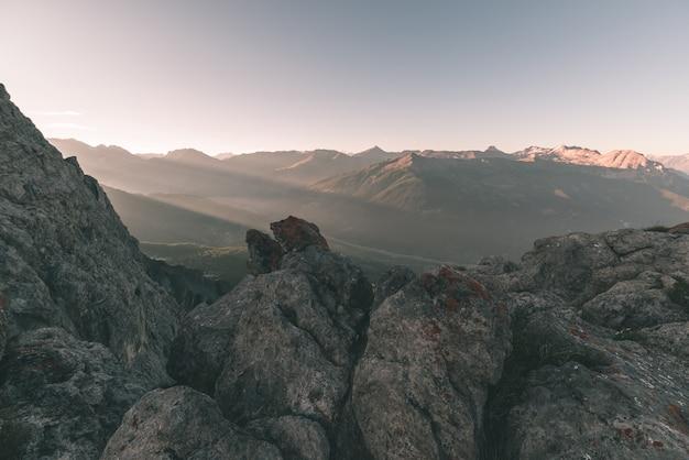 Альпийские луга и пастбища расположены среди высокогорных горных цепей на закаты. итальянские альпы, известное туристическое направление в летнее время. тонированное изображение, винтажный фильтр, разделенная тонировка.
