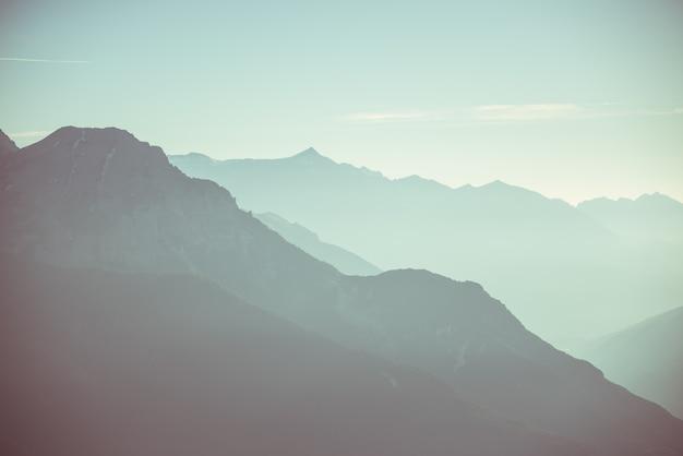 澄んだ空と柔らかな光の遠い山のシルエット。トーンの画像、ビンテージフィルター、スプリットトーン。
