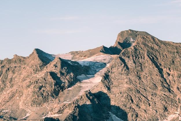 イタリアのフランスアルプスの死にゆく氷河に沈む夕日の光。気候変動の概念。彩度の低い彩度の低い画像。