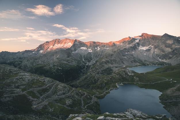 標高の高い高山湖、ダム、夕焼けに輝く雄大なロッキーマウンテンピークと牧歌的な土地の水盤。アルプスの広角ビュー。