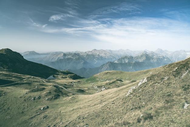 標高の高い牧草地、岩の多い山頂、ギザギザの尾根、風光明媚な空、イタリアアルプス。バックライトの拡大表示。彩度の低い彩度の低い画像。