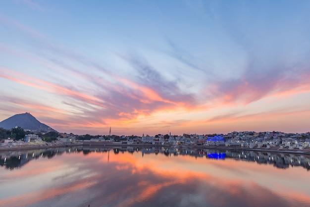 プシュカル、ラジャスタン、インドの上のカラフルな空と雲。夕暮れ時の湖の聖水を反映した寺院、建物、色。